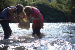A pair of students check their net for macroinvertebrates